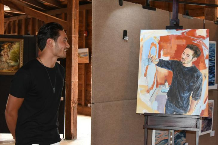 Artist jack Yuen stands by his portrait, painted by Elizabeth R. Whelan, at the event Artists in Art